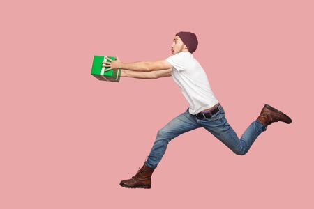 Photo pour Side view of portrait of crazy bearded young hipster man in white shirt and casual hat jumping, running and hurry up with delivery green present. Indoor, isolated, studio shot, pink background - image libre de droit