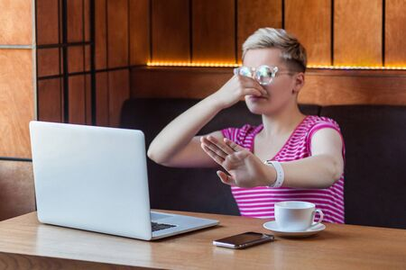 Photo pour bad smell. Portrait of unhappy confused young woman with short hair in pink t-shirt and eyeglasses is sitting in cafe, covering nose with finger and pleased to stop and pinching her nose. indoor - image libre de droit