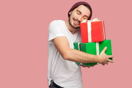 Photo for Portrait of happy satisfied handsome bearded young hipster man in white shirt and casual hat standing and holding two present bo and hugging it. Indoor, isolated, studio shot, pink background - Royalty Free Image
