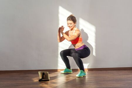 Foto de Positive sportive woman with bun hairstyle and in tight sportswear doing squatting sit-up exercise while watching training video on tablet. indoor studio shot illuminated by sunlight from window - Imagen libre de derechos