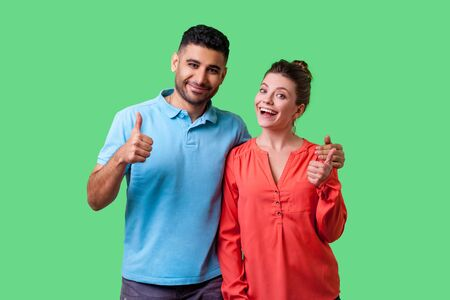 Photo for Portrait of positive attractive young couple in casual wear standing together, hugging as friends, showing thumbs up gesture and smiling at camera. isolated on green background, indoor studio shot - Royalty Free Image