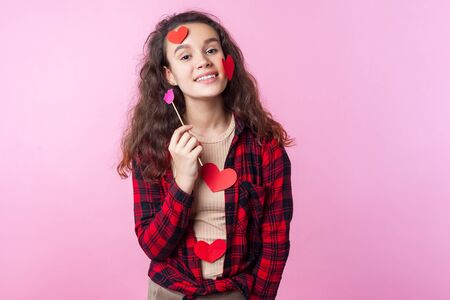Photo pour Valentines Day. Portrait of charming teenage girl with curly brunette hair and heart stickers on her face and clothes holding pink paper lips, smiling at camera. indoor studio shot, pink background - image libre de droit