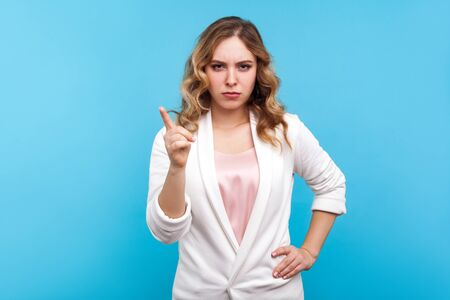 Photo pour I told you! Portrait of bossy woman with wavy hair in white jacket frowning face and pointing finger up in warning gesture, teacher scolding with displeased expression. studio shot, blue background - image libre de droit