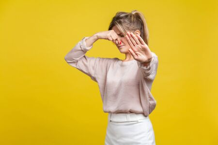Photo pour Stinky smell. Portrait of young dissatisfied woman with fair hair in casual beige blouse standing, pinching her nose with disgust and gesturing stop. indoor studio shot isolated on yellow background - image libre de droit