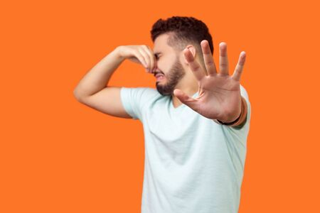 Photo pour Stinky smell. Side view of confused brunette man with beard in white t-shirt holding breath with fingers on nose, disgusted by bad odor fart, gesturing stop. studio shot isolated on orange background - image libre de droit
