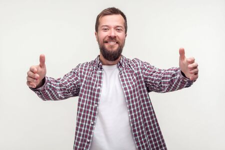 Photo pour Come into my arms! Portrait of happy good-natured bearded man in plaid shirt raising hands wide for hug and smiling friendly at camera, hospitable expression. indoor studio shot, white background - image libre de droit