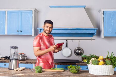 Photo pour Positive man standing in modern kitchen holding tablet pc and looking at camera with smile, searching food recipe on internet, reading calories, basket of fresh green vegetables on table, healthy diet - image libre de droit