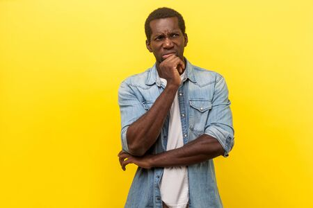 Foto de Portrait of puzzled pensive man in denim casual shirt with rolled up sleeves looking up and thinking intensely with doubting uncertain expression. indoor studio shot isolated on yellow background - Imagen libre de derechos