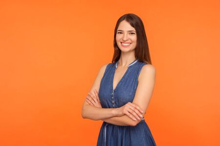 Photo pour Attractive brunette woman in denim dress standing half turned with crossed hands and smiling with white teeth, being healthy happy satisfied, expressing joy. studio shot isolated on orange background - image libre de droit