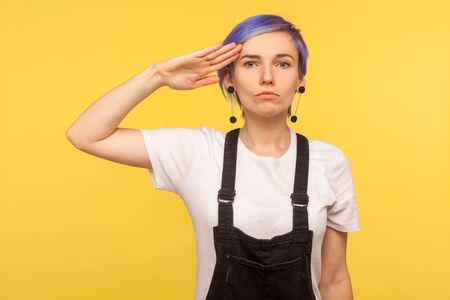 Foto per Yes sir! Portrait of serious obedient hipster girl with violet short hair in denim overalls keeping hand near temple and saluting as soldier, listening to commander. yellow background, studio shot - Immagine Royalty Free
