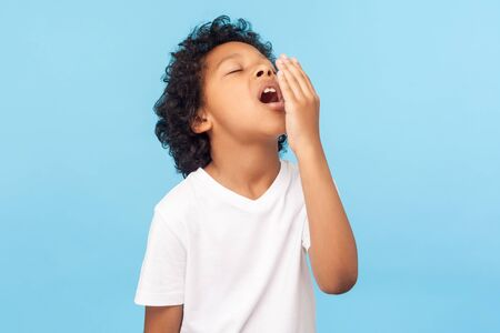 Photo for Portrait of sleepy tired little boy with curly hair in white T-shirt covering mouth with hand while yawning with eyes closed, drowsy child waking up. indoor studio shot isolated on blue background - Royalty Free Image