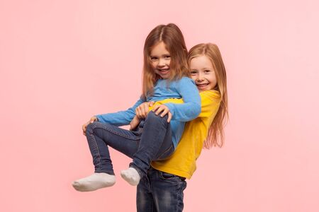 Foto de Portrait of cute preschool girl lifting up her little sister and smiling, friends having fun together, playing game, expressing carefree childish happiness. studio shot isolated on pink background - Imagen libre de derechos