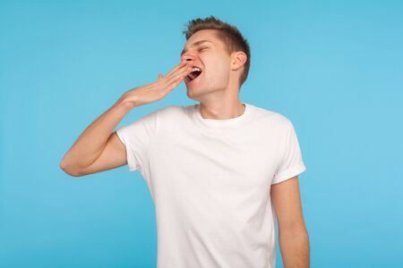 Photo for Exhausted sleepy man in casual white t-shirt standing with closed eyes and yawning, covering mouth with hand, suffering insomnia, lack of energy. indoor studio shot isolated on blue background - Royalty Free Image