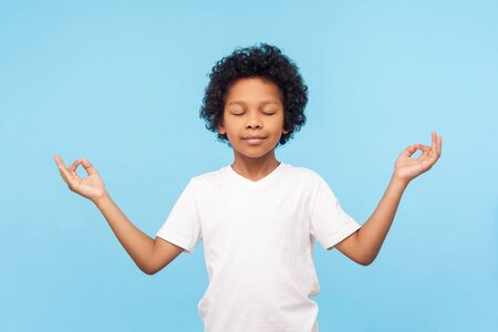 Photo for Portrait of peaceful cute little boy holding fingers in mudra gesture and meditating with closed eyes, feeling calm positive and relaxed, yoga practice. indoor studio shot isolated on blue background - Royalty Free Image