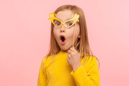 Photo pour Surprised little girl covering eyes with paper glasses and sticking out tongue, naughty child having fun, wearing masquerade mask and looking shocked. indoor studio shot isolated on pink background - image libre de droit