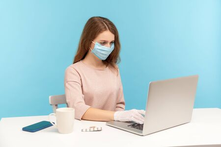 Photo pour Office worker wearing facial mask and hygienic gloves while typing on laptop, protecting her hands and face to prevent contagious disease, viral infection, coronavirus 2019-ncov. indoor studio shot - image libre de droit