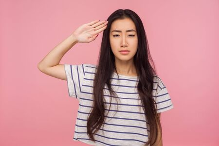 Foto per Yes sir! Responsible serious girl with brunette hair in striped t-shirt giving salute with attentive look, listening to command, ready to obey order. indoor studio shot isolated on pink background - Immagine Royalty Free