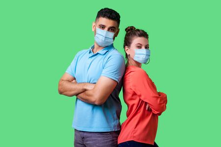 Photo pour Cheerful young couple of friends with surgical medical mask standing back to back with crossed hands and looking at camera . isolated on green background, indoor studio shot - image libre de droit