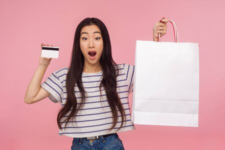 Photo pour Incredible credit for purchases! Portrait of amazed pretty girl holding bank card and packages, shocked by shopping loan, profitable cashback. indoor studio shot, isolated on a pink background. - image libre de droit