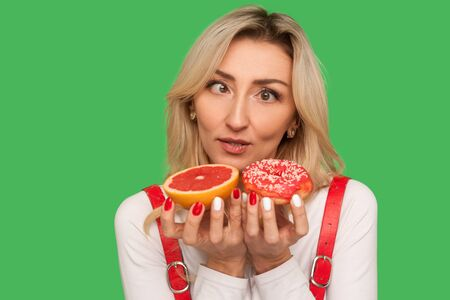 Photo for Closeup of confused adult woman looking with crossed eyes at grapefruit and doughnut, expressing doubts, choosing confectionery vs healthy fruit. indoor studio shot isolated on green background - Royalty Free Image