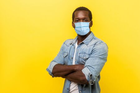 Photo pour Portrait of man in casual shirt with surgical medical mask standing with crossed hands and looking at camera. medical and healthcare concept. indoor studio shot isolated on yellow background - image libre de droit