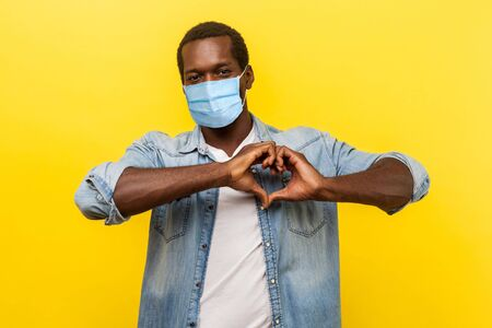 Photo for Portrait of handsome cheerful man with surgical medical mask making heart shape with hands, expressing love feelings or friendship. indoor studio shot isolated on yellow background - Royalty Free Image