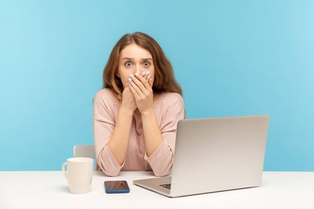 Photo pour Scared upset young woman employee sitting at workplace with laptop and covering mouth with hand, afraid to tell corporate secret. indoor studio shot isolated on blue background - image libre de droit