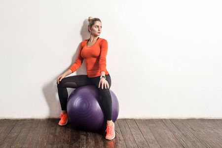 Beautiful slim sporty woman in tight sportswear sitting on big fitness rubber ball, taking break and resting after training in gym home. Health care, sports activity and workouts. indoor studio shot