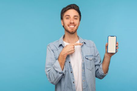 Foto de Portrait of cheerful happy man in worker denim shirt smiling and showing mobile device, cell phone with mock up empty display to advertise. indoor studio shot isolated on blue background, copy space - Imagen libre de derechos