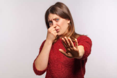 Photo pour Portrait of girl grimacing in disgust and pinching her nose, showing stop hand gesture confused by bad breath, stinky odor, repulsion to awful fart gases. studio shot isolated on gray background - image libre de droit