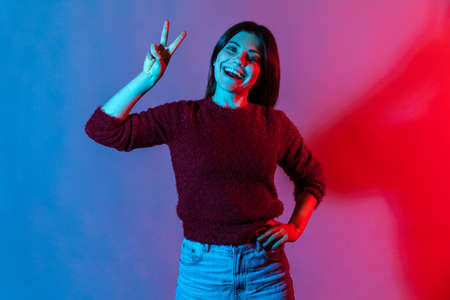 Neon light portrait of carefree happy pretty woman showing victory or peace gesture and smiling broadly, rejoicing lucky winning, feeling optimistic about future success. indoor studio shot isolated