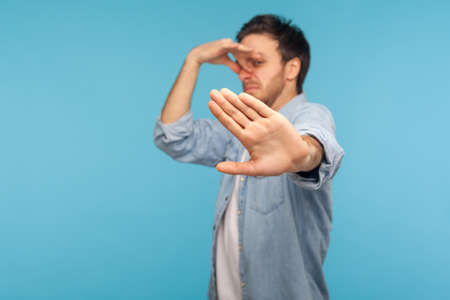 Photo pour Stop this awful stink! Portrait of man in denim shirt grimacing in disgust, showing rejection with raised palm, pinching nose to avoid bad smell, fart gases, expressing repulsion. studio shot isolated - image libre de droit