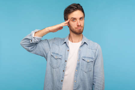 Foto per Yes sir! Portrait of responsible patriotic man in worker denim shirt saluting with respect as if soldier waiting order from commander, obeying discipline. studio shot isolated on blue background - Immagine Royalty Free