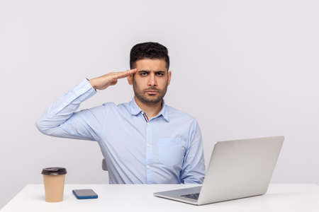 Foto per Yes sir! Responsible man employee sitting office workplace with laptop on desk, looking at camera with salute and ready to do your order, following discipline. studio shot isolated on white background - Immagine Royalty Free