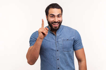 Photo pour Eureka. Clever smiling man with beard pointing finger up, has good idea genius plan, inspiration and creativity. Indoor studio shot isolated on white background - image libre de droit