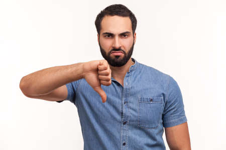 Photo pour Unhappy dissatisfied man with beard showing thumbs down dislike gesture, symbol of disagree, giving feedback. Indoor studio shot isolated on white background - image libre de droit