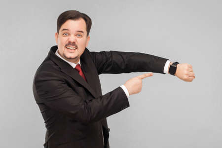 Photo pour Not have a many time, hurry please! indoor studio shot. isolated on gray background. handsome businessman with black suit, red tie and mustache looking at camera. - image libre de droit