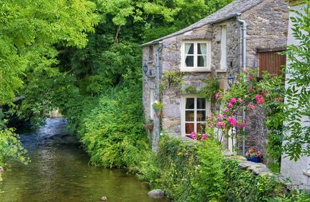 An old, quaint English cottage on the bank of a small river in Cartmel, England.