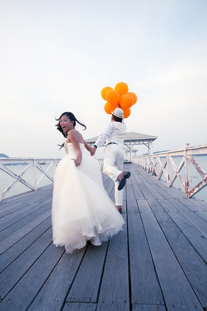 Foto de couple of man and women in wedding suit glad emotion on wood bridge - Imagen libre de derechos
