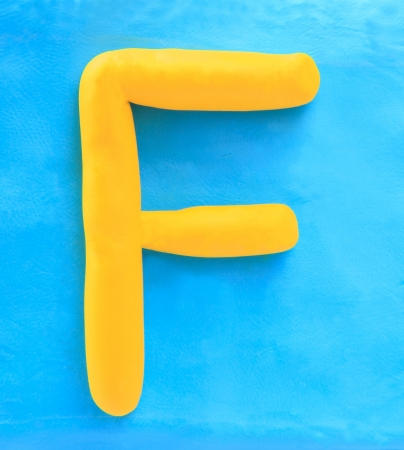 yellow clay alphabet letter with drop shadow on blue clay