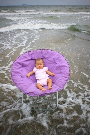 baby sitting on round chairs at sea beach