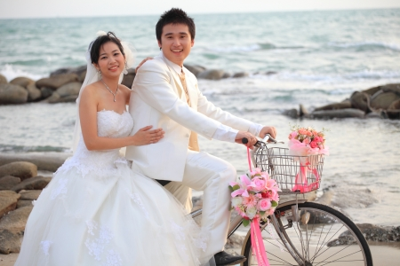 couple of young man and woman in wedding suit ridiing old bicycle on sand beachの写真素材