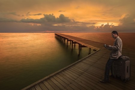 man reading a guide book on wood bridge before travel to another place