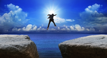 business man jumping to next cliff with risk decision