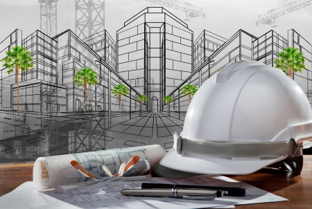 safety helmet and architect plan on wood table with sunset scene and building construction