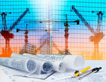 Photo pour architecture plan on architect working table with building and reflection of crane construction on mirror building - image libre de droit