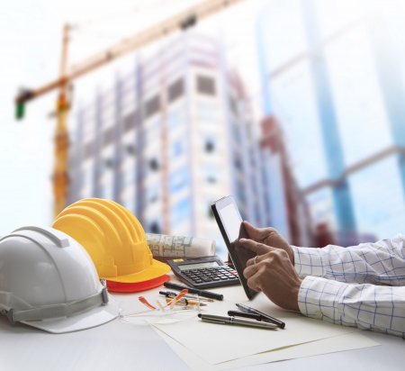 Photo pour hand of architect working on table with tablet computer and working tool equipment against reflection of office building and crane construction for civil engineering and construction industry business  - image libre de droit