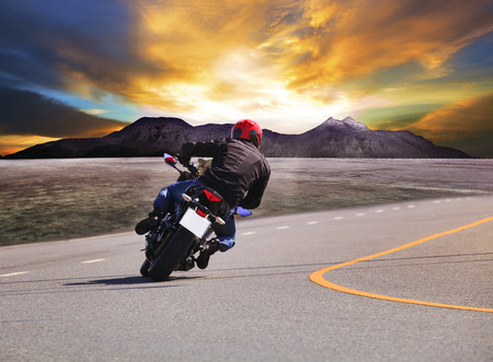 rear view of young man riding motorcycle in asphalt road curve with rural and mountain scene  background