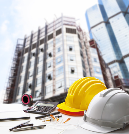 Photo pour safety helmet and writing instrument on engineering working table against exterior construction building - image libre de droit