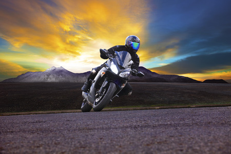 young man riding motorcycle in asphalt road curve with rural and mountain background